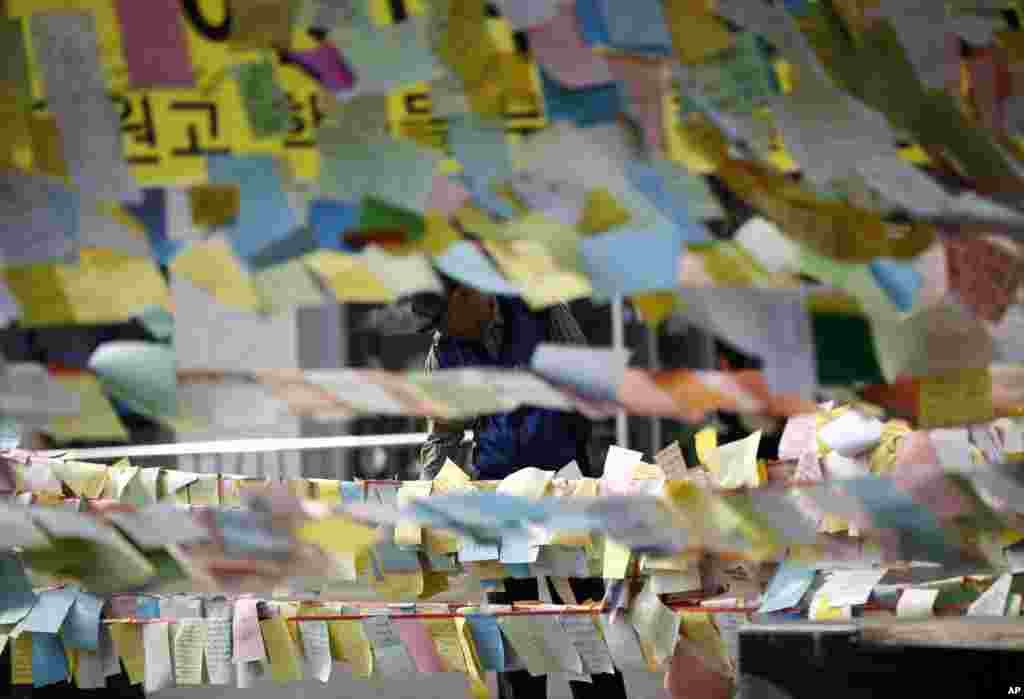 A man reads messages showing signs of hope for the safe return of passengers of the sunken ferry boat Sewol in Ansan, South Korea, April 24, 2014.