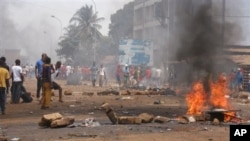 FILE - Anti-government protesters burn tires and place rocks in the streets in Conakry, Guinea, May 3, 2013