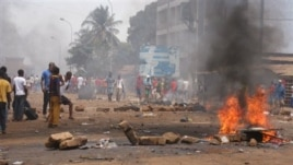 Anti government protesters burn tires and place rocks in the streets in Conakry, Guinea, May 3, 2013