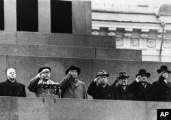 Red China's Mao Tse-Tung (third from left) stands with top Russian leaders to salute from Lenin Mausoleum as parade passes below on Nov. 11,1957 in Red Square at Moscow.