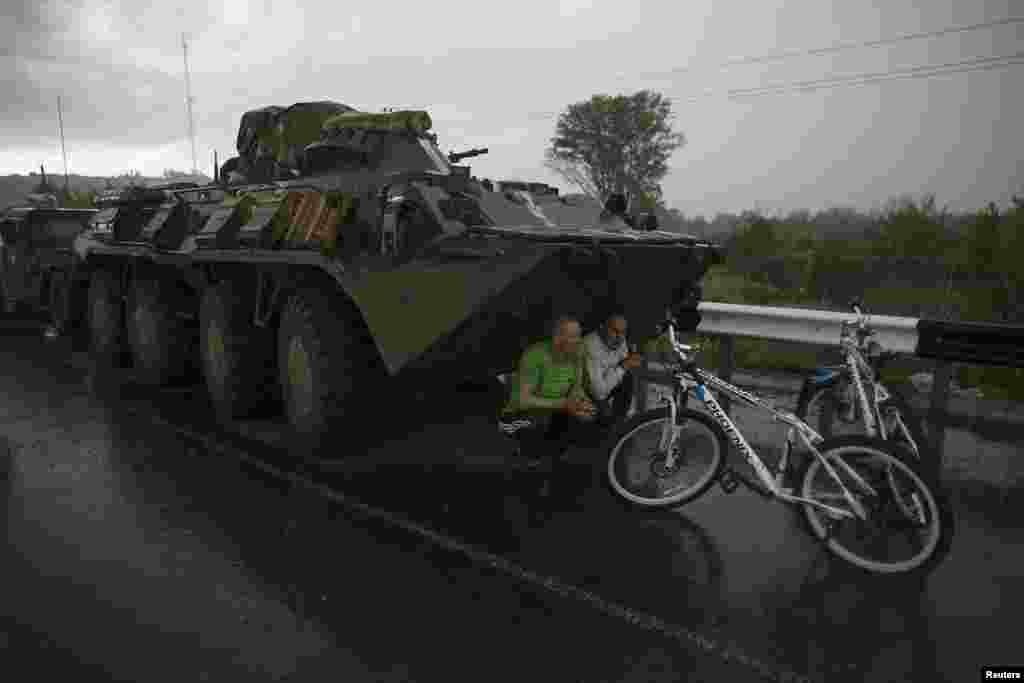Civilians find cover from the rain under a Ukrainian army armored personnel carrier at a checkpoint near the town of Slaviansk.