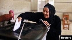 Seorang wanita memasukkan surat suaranya ke dalam kotak suara pemilu presiden Mesir yang bersejarah di sebuah TPS di Kairo (24/5).