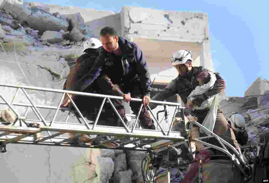Syrian Civil Defense members evacuate a toddler from the rubble of buildings destroyed following Russian air strikes in the northwestern city of Idlib, on May 30, 2016.
