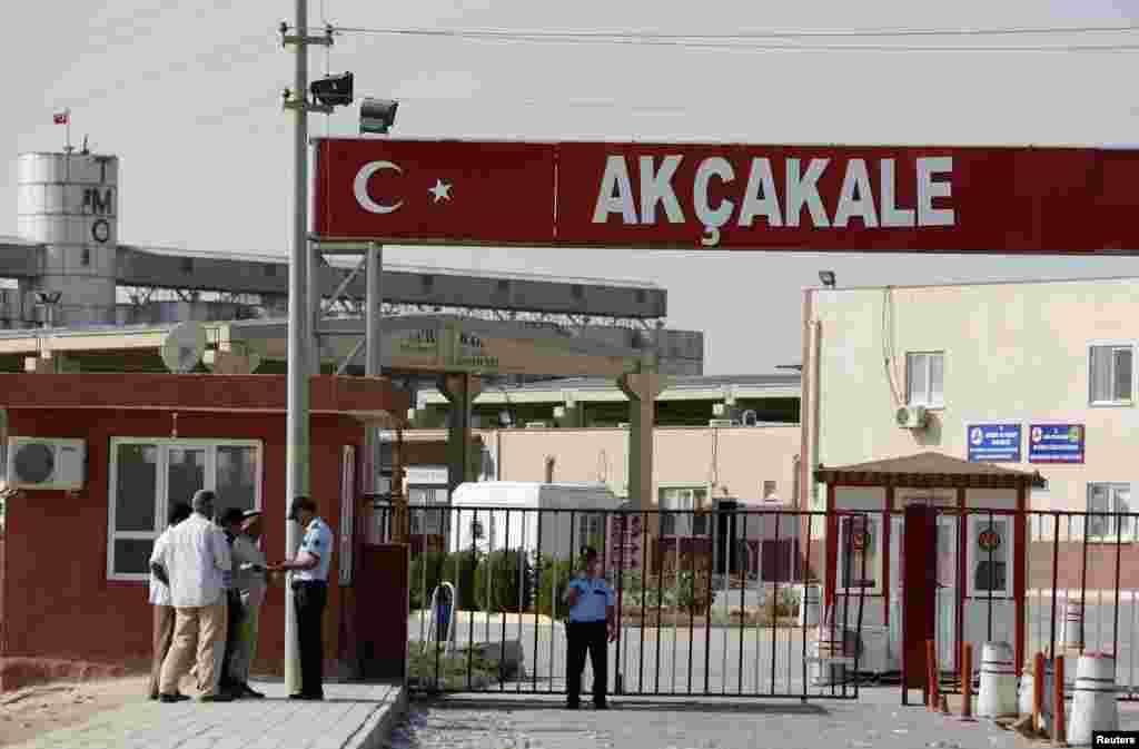 ຕຳຫຼວດເທີກີຄົນນຶ່ງ ກວດເບິ່ງບັດປະຈຳຕົວຂອງພວກຜູ້ຊາຍຊາວຊີເຣຍ ທີ່ຂ້າມຊາຍແດນຈາກຊີເຣຍ ເຂົ້າໄປໃນເທີກີ ທີ່ດ່ານຂ້າມຊາຍແດນ Akcakale (4 ຕຸລາ 2012)