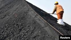 一名中國工人在山東日照港鏟著從澳大利亞進口的煤炭(資料圖片)