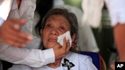 Former Social Affairs Minister Ieng Thirith, center, Ieng Sary's wife, cries during the cremation ceremony of his husband at his home of a former stronghold of Malai, 420 kilometers (260 miles) from Cambodian-Thai border, northwestern of Phnom Penh, Cambodia, Thursday, March 21, 2013. Ieng Sary, who co-founded the communist Khmer Rouge regime responsible for the deaths of an estimated 1.7 million Cambodians in the 1970s, and who decades later became one of its few leaders to be put on trial, died on March 14 before his case could be finished. He was 87. (AP Photo)