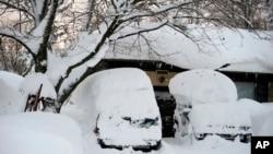 Mobil-mobil yang tertimbun salju di Lancaster, New York (19/11). (AP/Gary Wiepert)