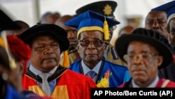 Zimbabwe's President Robert Mugabe, center, arrives to preside over a graduation ceremony at Zimbabwe Open University on the outskirts of Harare, Zimbabwe Friday, Nov. 17, 2017. Mugabe is making his first public appearance since the military put him under house arrest earlier this week. (AP Photo/Ben Curtis)