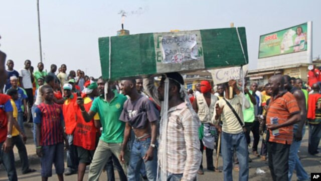 A man carries a coffin as protesters march through a road on the third day of a protest against a removal of fuel subsidies in Nigeria's commercial capital Lagos, January 11, 2012.