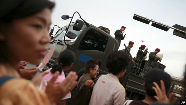 Thai soldiers entertain passers-by while providing security at Bangkok's Victory Monument in Thailand Thursday, June 5, 2014.