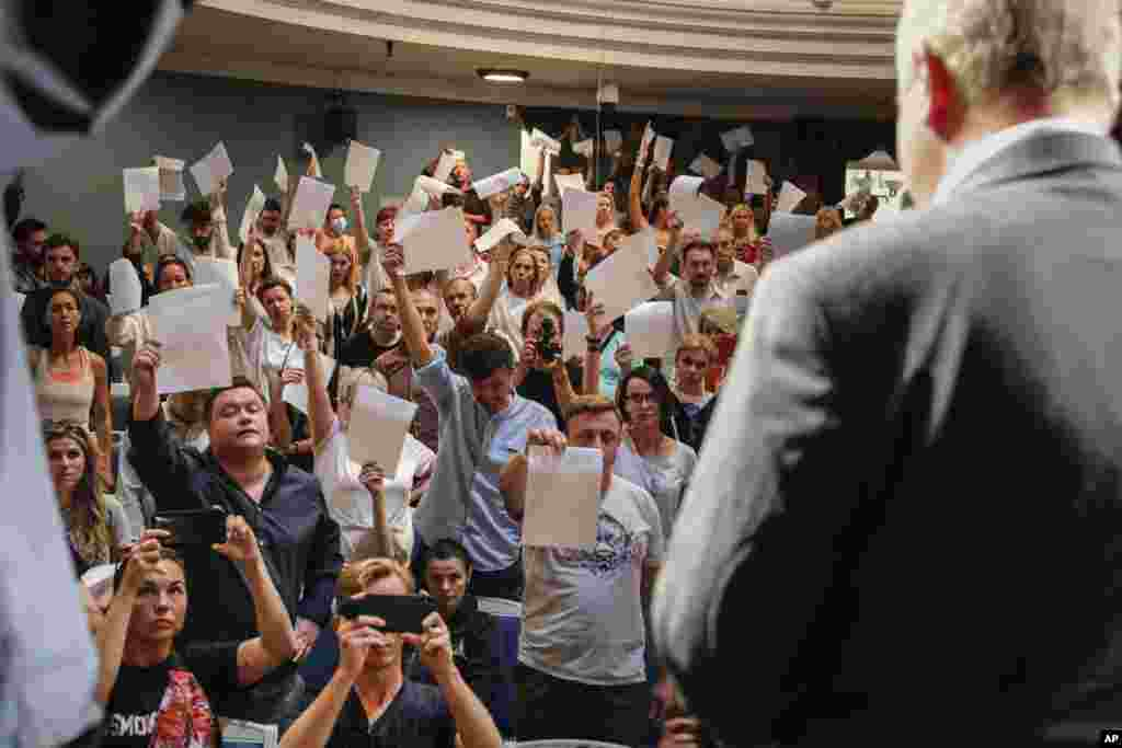 Theater workers show their resignation letters to Yuri Bondar, Belarusian Minister of Culture, in the Janka Kupala National Theater in Minsk after the theater's director, Pavel Latushko, was fired.