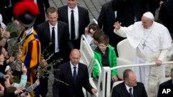 Paus Fransiskus, dikelilingi anak-anak yang ia undang untuk mendekati mobil dinasnya. Lapangan Santo Petrus, Vatikan.