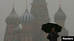 FILE - A man walks under an umbrella during a snowfall in Red Square in central Moscow March 31, 2014.