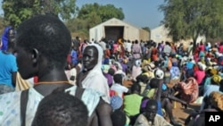 FILE - Women wait for grain to feed their families, at Doro refugee camp in South Sudan.