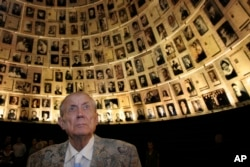 "FILE - Poet Yevgeny Yevtushenko looks at photographs of Jewish Holocaust victims during a visit to the Yad Vashem Holocaust Memorial in Jerusalem, Nov. 15, 2007. During his visit, Yevtushenko read the poem ""Babi Yar,"" a poem against anti-Semitism he published in 1961."