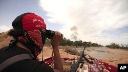 利比亚反政府武装的战士周六用望远镜观察米苏拉塔发生的爆炸