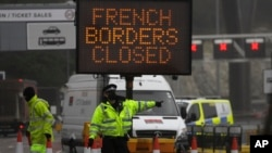 A police officer directs traffic at the entrance to the closed ferry terminal in Dover, England, Monday, Dec. 21, 2020, after the Port of Dover was closed and access to the Eurotunnel terminal suspended following the French government's announcement. Fran