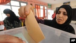 A Moroccan posts her ballot at a voting station in Sale, near Rabat, July 1, 2011