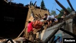 在湖南涟源,暴雨后,灾民从倒塌的房子里搬东西(2017年7月3日)