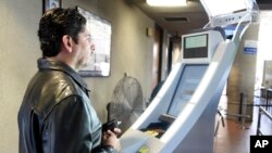 A pedestrian crossing from Mexico into the United States at the Otay Mesa Port of Entry has his facial features and eyes scanned at a biometric kiosk in San Diego, California, Dec. 10, 2015. Senior U.S. administration officials have shed more light on the K-1 visa application process, which has come under scrutiny following this month's mass shooting in San Bernardino, California.