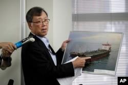 Yutaka Katada, president of Kokuka Sangyo Co., the Japanese company operating one of two oil tankers attacked near the Strait of Hormuz, shows a photo of the attacked oil tanker during a news conference Friday, June 14, 2019, in Tokyo. (AP Photo/Jae C. Ho