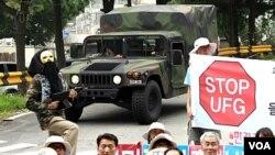 Manifestantes reclaman en Corea del Sur contra los ejercicios militares, mientras un vehículo militar estadounidense pasa frente al grupo.