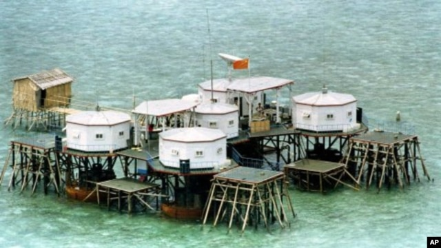 A Chinese flag and a satellite dish are prominently displayed in a structure built by China in one of the islands in the Spratly Islands.