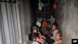 Para tahanan berjongkok di lantai penjara rahasia saat ditemukan oleh Komisi Hak Asasi Manusia di Kantor Polisi 1 di distrik Tondo di Manila, Filipina, 27 April 2017. (AP Photo/Ezra Acayan)
