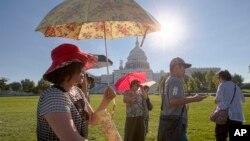2016年8月12日,韩国游客在华盛顿参观国会山打着伞躲避早晨的阳光。