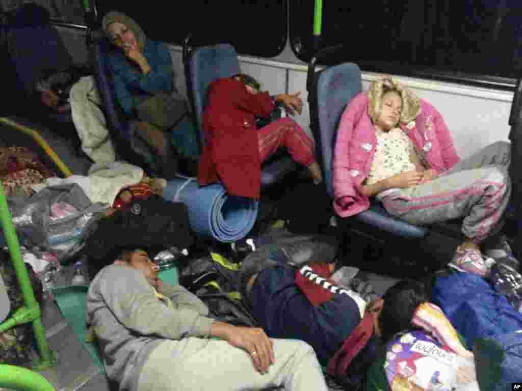 مهاجرانی که با اتوبوس راهی مرز اتریش می شوند، از خستگی کف اتوبوس خوابیده اند.