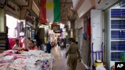 A Kurdish man wearing traditional clothes passes under a Kurdish flag in Irbil's old bazaar, IraqThursday, Aug. 24, 2017. Despite calls from Baghdad and the United States to postpone the vote, Iraq's semi-autonomous Kurdish region is pressing ahead with plans to hold a referendum on independence September 25.