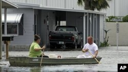 Rains from Tropical Storm Debby force residents of New Port Richey, Florida to make their way through a flooded street in a boat, June 26, 2012 (AP).