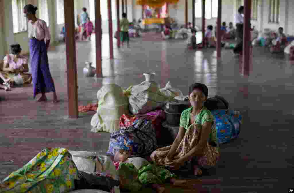 A Rakhine Buddhist woman and her child take in a monastery because of the arrival of the Cyclone Mahasen, Sittwe, Burma, May 14, 2013.
