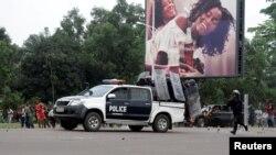 Un policier congolais court pour rejoindre ses camarades dans un véhicules lors des affrontements avec des militants de l'opposition exigeant le départ du président Joseph Kabila du pouvoir à Kinshasa, RDC, 19 Septembre 2016.