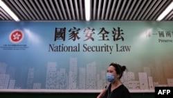 行人走過香港街頭港版國安法的宣傳牌。 (2020年7月28日)