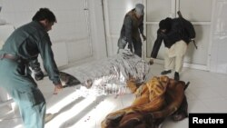 Afghan policemen carry the dead body of a victim at a local hospital after a suicide bomb attack in Khost province, December 26, 2012.