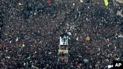 1月5日,在伊朗的玛瑟赫德市,苏莱曼尼和其他人的棺材被抬上了卡车。周围是悼念的人群。