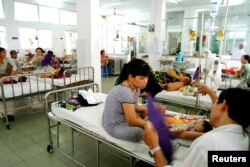 FILE - Vietnamese parents look after their children in a room designated for the treatment of dengue fever at Ho Chi Minh City's pediatric hospital, March 12, 2004.