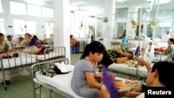 Vietnamese parents look after their children in a room designated for the treatment of dengue fever