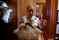 U.S. Supreme Court Justice Ruth Bader Ginsburg shows the many different collars (jabots) she wears with her robes, in her chambers, at the Supreme Court building in Washington, U.S. June 17, 2016.