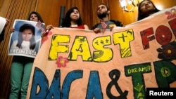 DACA recipients hold up a sign after an event by Democrats calling for congressional Republicans to bring forward immigration legislation on Capitol Hill in Washington, Sept. 6, 2017.