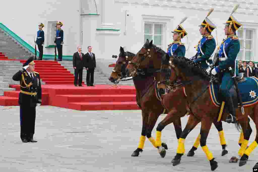 Presiden Rusia Vladimir Putin (kiri) dan mantan Presiden Dmitry Medvedev menyaksikan parade pengawal kehormatan Kremlin di Lapangan Katedral setelah upacara pelantikan.