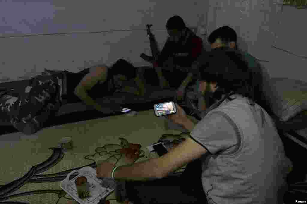 យុទ្ធជន Harakat Nour al-Din al-Zenki មើលព័ត៌មានតាមទូរសព្ទដៃស្មាតហ្វូនរបស់ខ្លួន ដែលផ្សាយពីជ័យជម្នះរបស់លោកដូណាល់ ត្រាំជាប្រធានាធិបតីអាមេរិក ក្នុងតំបន់កាន់កាប់ដោយក្រុមឧទ្ទាម ក្នុងក្រុង Aleppo ប្រទេសស៊ីរី កាលពីថ្ងៃទី០៩ ខែវិច្ឆិកា ឆ្នាំ២០១៦។