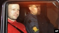 Norwegian Anders Behring Breivik (L), the man accused of a killing spree and bomb attack in Norway, sits in the rear of a vehicle as he is transported in a police convoy as he is leaving the courthouse in Oslo July 25, 2011