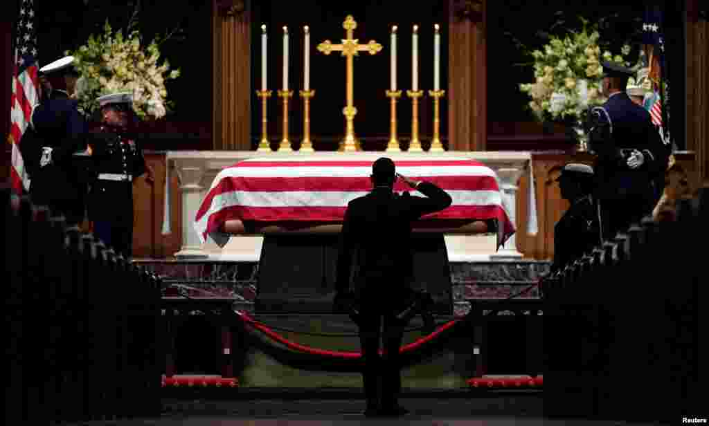 People pay their respects as the flag-draped casket of former President George H.W. Bush lies in repose at St. Martin's Episcopal Church in Houston, Dec. 5, 2018.