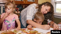 FILE - A mother works with her children during a homeschool assignment in St. Charles, Iowa, Sept. 30, 2011.