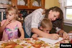 "This mother in Iowa is homeschooling her children. To ""homeschool"" means to teach your children at home and not send them to a public or private school. (2011 Photo: REUTERS/Brian C. Frank)"