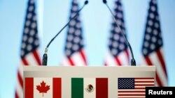 ທຸງຊາດ ການາດາ, ເມັກຊິໂກ ແລະ ສະຫະລັດ ຢູ່ດ້ານຫຼັງ ຂອງແທ່ນກ່າວຄຳປາໄສ ກ່ອນກອງປະຊຸມ ຖະແຫຼງຂ່າວ ໃນພິທີປິດ ການເຈລະຈາຮອບທີ 7 ຂອງ ອົງການ NAFTA, ທີ່ນະຄອນຫຼວງ ເມັກຊິໂກ ຊີຕີ້, ປະເທດ ເມັກຊິໂກ. 5 ມີນາ, 2018.