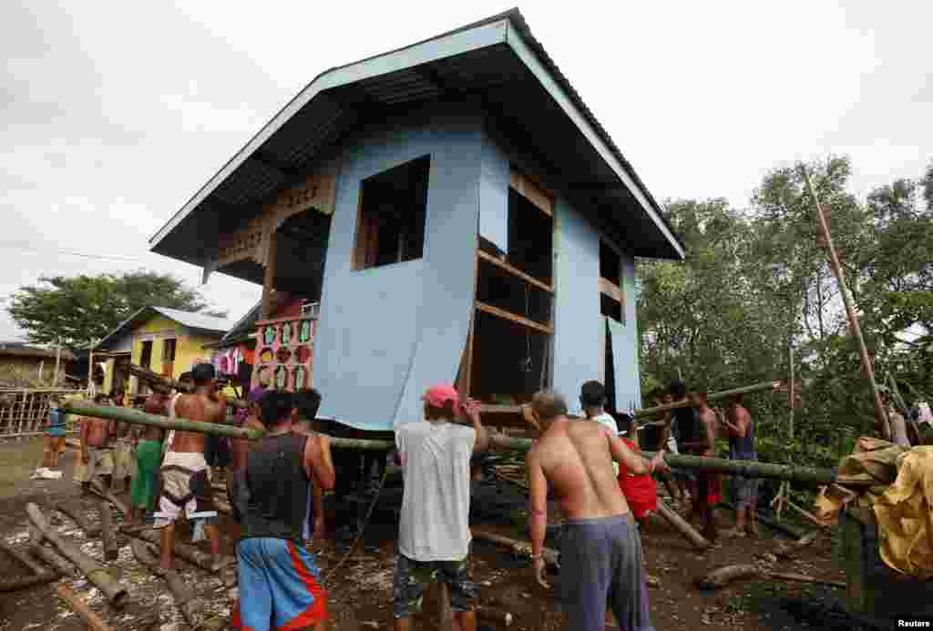 Residents lift a house damaged by Typhoon Rammasun in Batangas city, south of Manila, July 17, 2014.