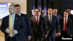 美國財政部長努欽(中)和美國經貿代表團成員離開北京一家酒店前去與中方談判人員舉行貿易談判。 (2018年5月3日)